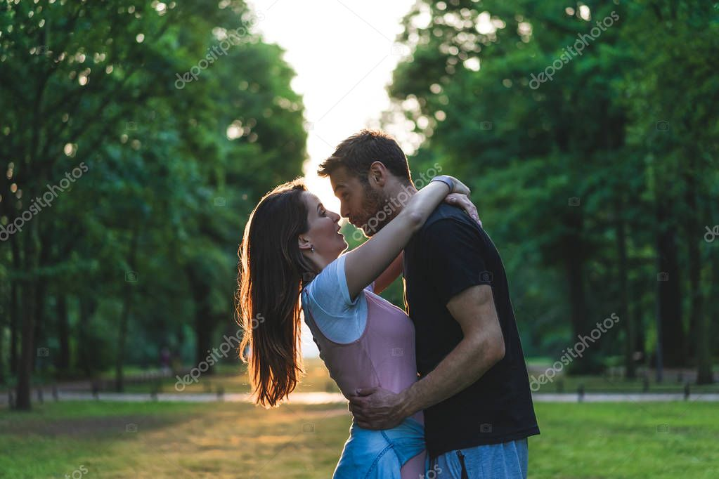 side view of young couple hugging each other and having fun on meadow