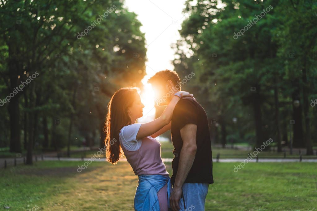 side view of smiling woman embracing boyfriend during sunset time