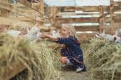 boční pohled na usmívající se dítě sedí na zemi ve stodole a dojemné koz