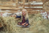 Photo smiling kid sitting on ground near goats in barn and looking at camera