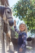 smiling kid touching white horse at farm and looking at camera