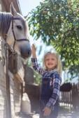 Fotografia bambino sorridente toccare white horse farm e rivolto verso lobiettivo