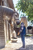 side view of kid touching white horse at ranch