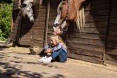 smiling kid sitting on ground and horse touching her hair at farm