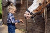 side view of child going to touch horse at farm