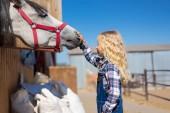 boční pohled dítěte dotýkat koně na ranči