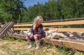 Fotografia kid sitting on fence at farm and looking at goats