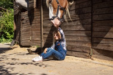 kid sitting on ground near stable and touching horse at farm