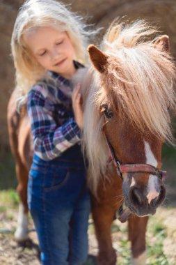 Kid touching cute pony fur at farm stock vector