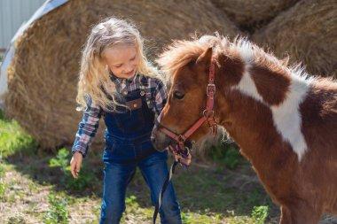 Happy kid standing near cute pony at farm stock vector