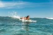 Fotografie male athlete swimming on surfing board in ocean at Nusa Dua Beach, Bali, Indonesia