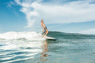 shirtless male surfer riding waves in ocean at Nusa Dua Beach, Bali, Indonesia