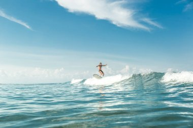 distant view of male surfer riding waves in ocean at Nusa Dua Beach, Bali, Indonesia