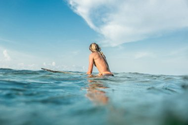 rear view of shirtless male surfer swimming on surfing board in ocean at Nusa Dua Beach, Bali, Indonesia
