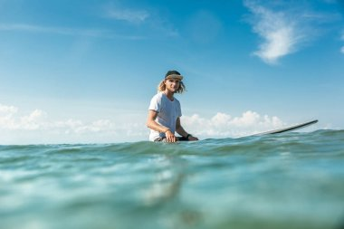 selective focus of young male surfer sitting on surfing board in ocean at Nusa Dua Beach, Bali, Indonesia