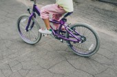 Fotografie cropped shot of child riding bicycle on city street