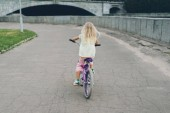 Photo back view of blond child riding bicycle on street