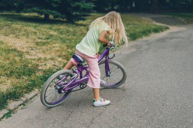 side view of cute kid with bicycle on street