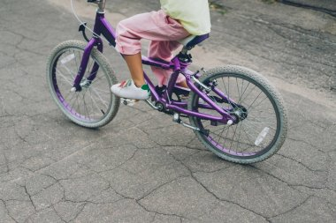 cropped shot of child riding bicycle on city street