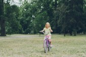smiling kid riding bicycle in summer park