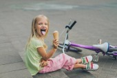 Fotografie cute child with ice cream sticking tongue out while sitting on city steps alone