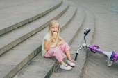 roztomilé dítě jíst zmrzlinu zatímco sedí na schodech město poblíž kole