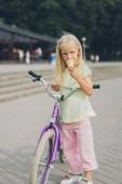 Fotografie rozkošné malé dítě se zmrzlinou a kolo stojí na bulváru