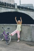 Fotografia adorable kid with ice cream showing peace sign near bicycle on street