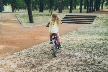 back view of kid riding bicycle in summer park