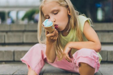 selective focus of cute child with ice cream sitting on city steps alone