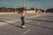happy little child riding on skateboard at parking lot