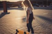 Fotografia vista laterale di piccolo bambino in piedi vicino a skateboard presso parcheggio