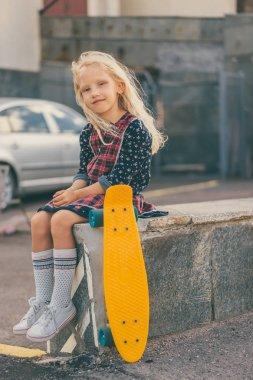 Smiling child sitting near skateboard and looking at camera at urban street stock vector