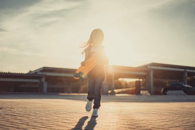 Little child running with skateboard in hands at parking lot against setting sun stock vector
