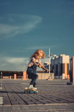 Smiling little child riding on skateboard at parking lot stock vector
