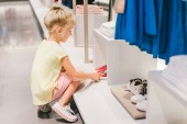 Photo side view of adorable little child choosing shoes in shop