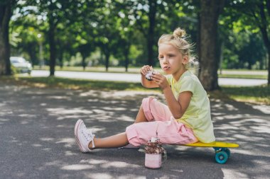 selective focus of adorable kid eating donut from dessert and looking away while sitting on skateboard at street