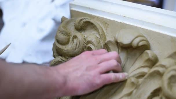 Bildhauer erstellen in Restaurierungswerkstatt Tonmodell einer korinthischen Kapitelle mit Schriftrollen und aufgerollten Akanthusblättern