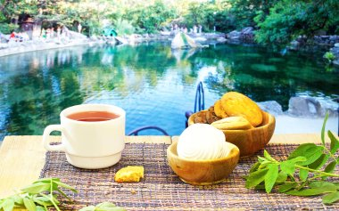 hot tea, teapot and sweets on a blue table on the background of a variety of beautiful landscapes