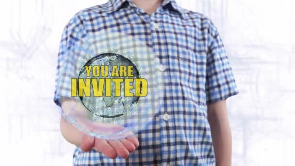 A fiatalember azt mutatja, hogy egy hologram, a Föld bolygó és a szöveg meghívást