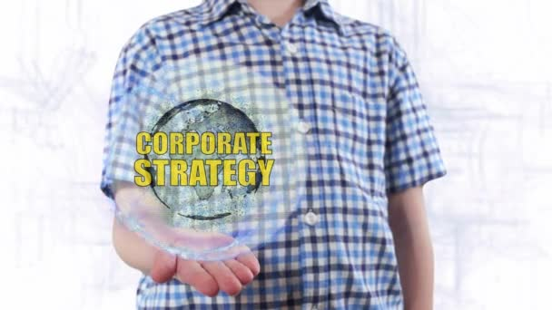 Young man shows a hologram of the planet Earth and text Corporate strategy