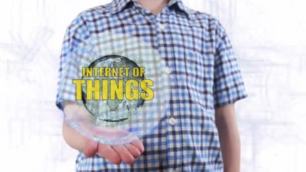 Mladý muž ukazuje hologram planety země a text Internet věcí