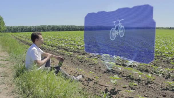 Man is working with 3D bike on holographic display on the edge of the field