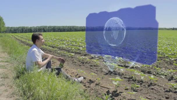 Man is working with 3D Earth on holographic display on the edge of the field