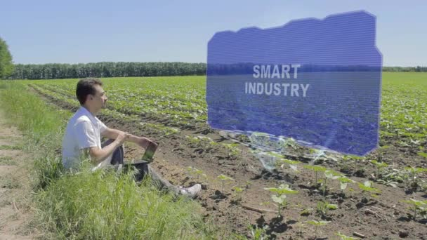 Man is working on HUD holographic display with text Smart Industry on the edge of the field. Businessman analyzes the situation on his plantation. Scientist examines future technology