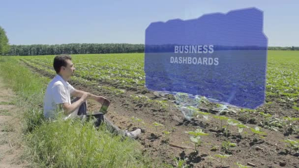 Man is working on HUD holographic display with text Business dashboards on the edge of the field