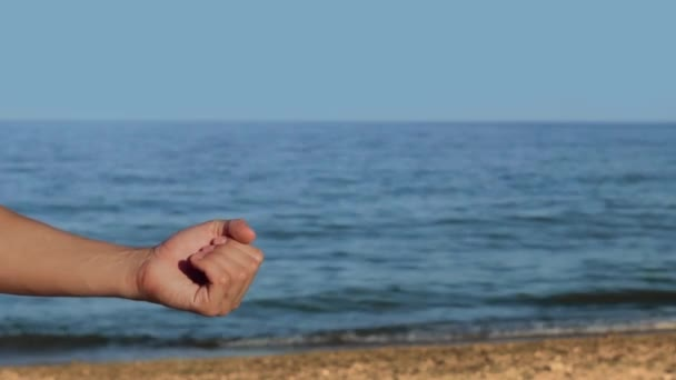 Male hands on the beach hold a conceptual hologram with the text IoT