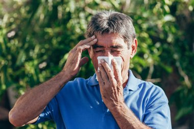 Elderly man blowing his nose on napkin on sunny day. Concept of respiratory disease.