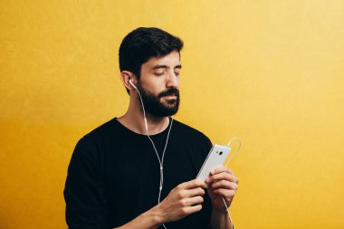 Man with closed eyes listening to music on his cellphone with headphones