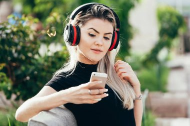 Woman listening to the music from a smart phone with headphones